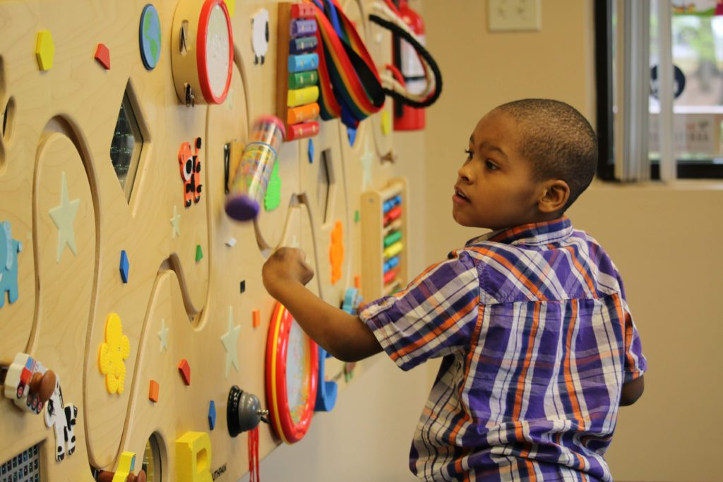child playing with wall toy