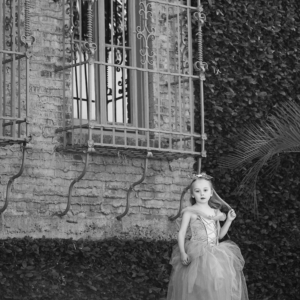 girl wearing a dress stands outside a stone wall