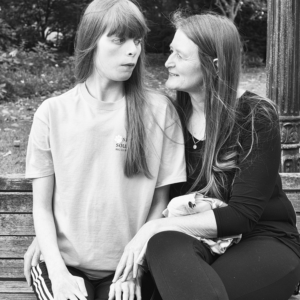 mother and daughter sit on a park bench