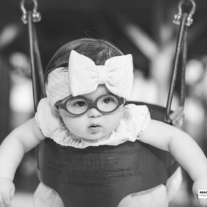 young girl sits in a swing