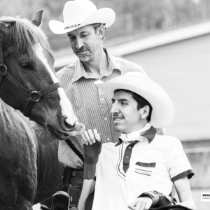 young man pets a horse with his father